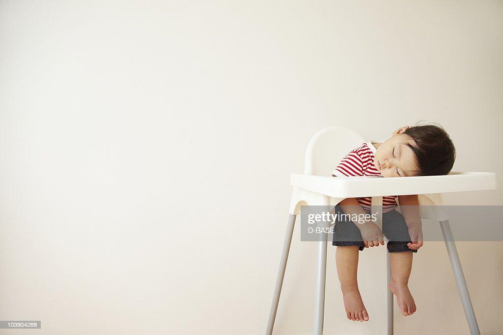 A baby boy sleeping in a high chair  : ストックフォト