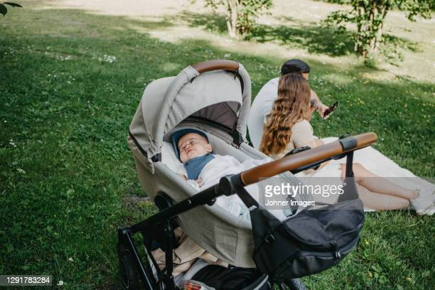 baby boy sleeping in pram, parents in background - carriage stock pictures, royalty-free photos & images