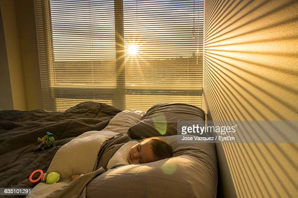 Baby Boy Sleeping On Bed At Home During Sunrise