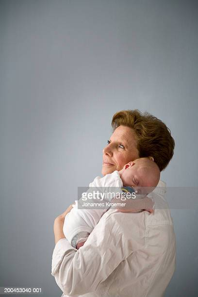 Baby (0-3 months) boy sleeping on grandmother's shoulder