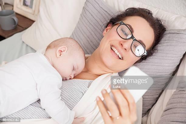 Baby boy sleeping on mother, mother using smartphone