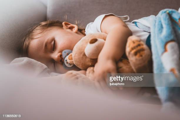 baby boy sleeping with teddy bear and pacifier - pacifier stock pictures, royalty-free photos & images