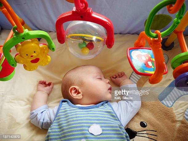 baby boy sleeps peacefully on playmat - babyhood stock pictures, royalty-free photos & images