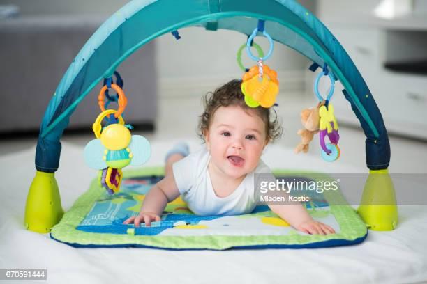 男の子は、笑みを浮かべて、ベビー サークルの中のおもちゃで遊んで