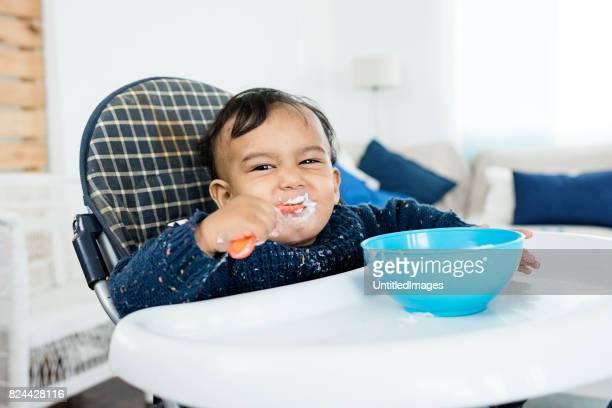 Jongetje glimlachend en zitten in een hoge stoel