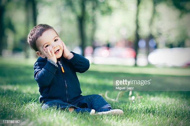 Baby boy smiling sitting on grass, Madrid