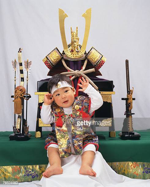 Baby boy smiling, wearing costume, background war helmet and swords, front view, portrait