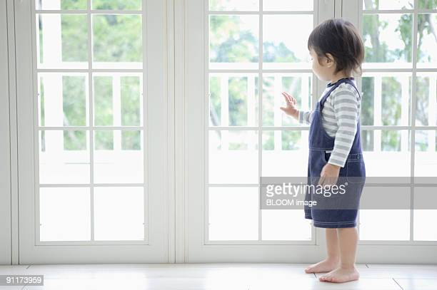 Baby boy standing by window, side view
