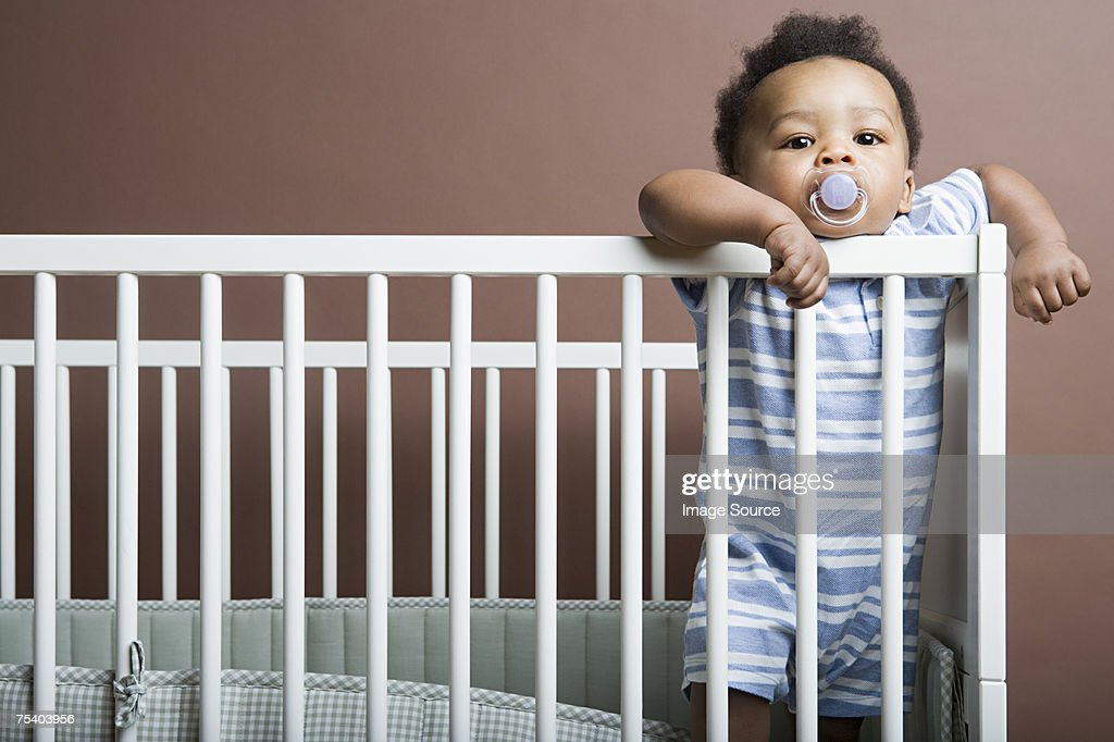Baby boy standing in cot : Stock Photo