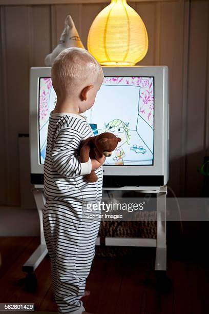 Baby boy standing in front of TV