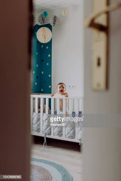 baby boy standing in his cot, laughing - ajar stock pictures, royalty-free photos & images