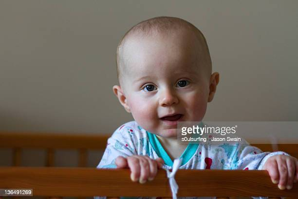 baby boy standing in his cot. - s0ulsurfing stock pictures, royalty-free photos & images