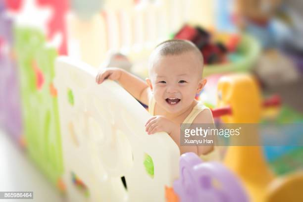 baby boy standing in playpen - waist up stock pictures, royalty-free photos & images