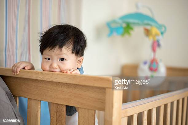 Baby boy standing on his cot