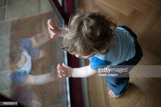 baby boy standing up holding on to window