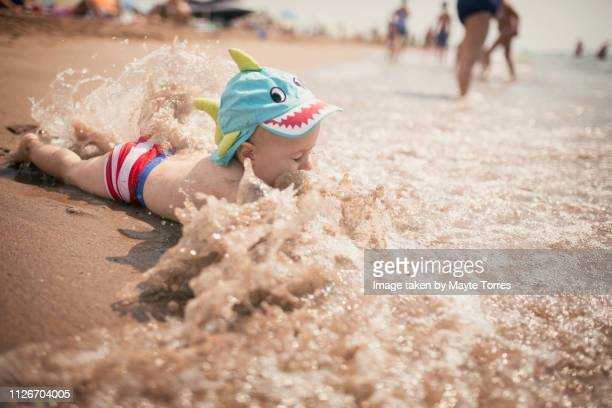 baby boy surprised by a wave while playing at the seashore - fish love ストックフォトと画像