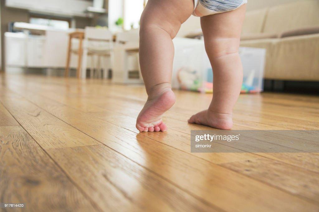 Primeiros passos do bebê menino tendo : Foto de stock