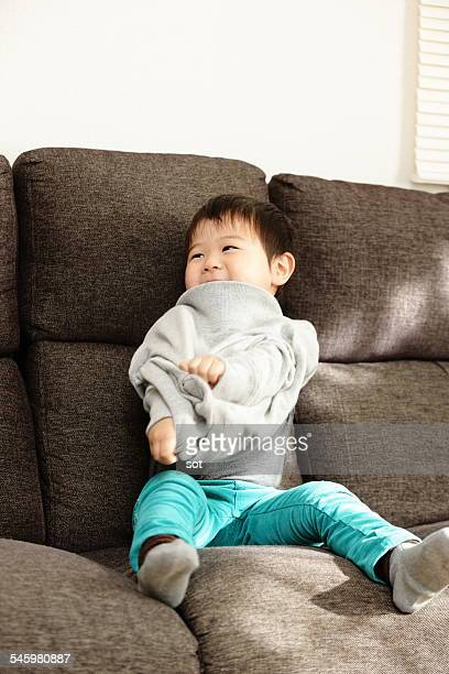 Baby boy taking of clothes in sofa