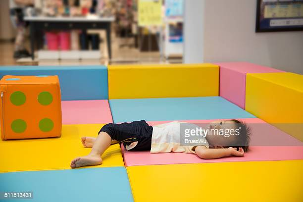 Baby boy tired and lying on playground