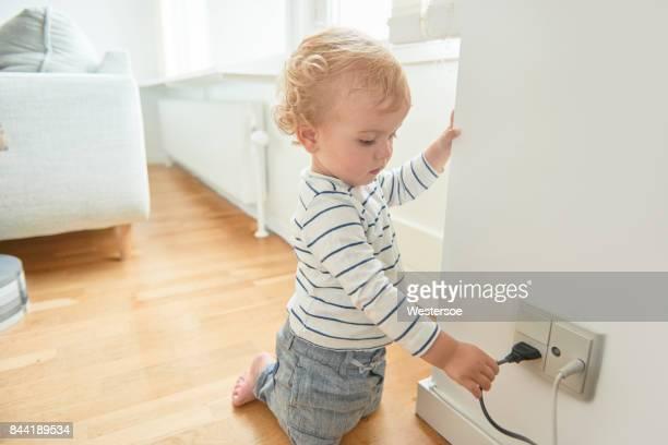 menino tocando elétricos plug na parede. - tomada - fotografias e filmes do acervo