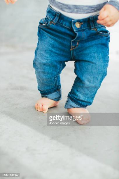 Baby boy trying to walk on floor
