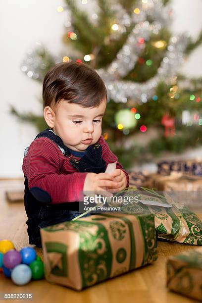 Baby boy unpacking Christmas presents