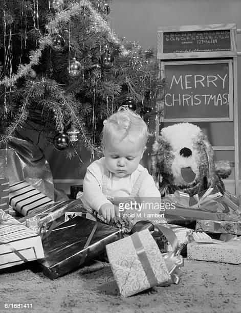 baby boy unwrapping christmas gift - escrita ocidental - fotografias e filmes do acervo