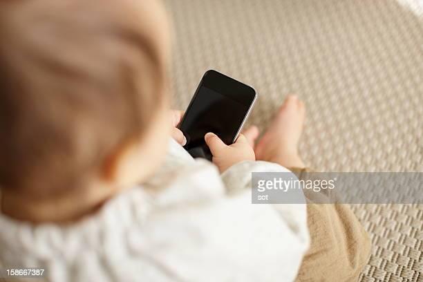Baby boy using smart phone,close up