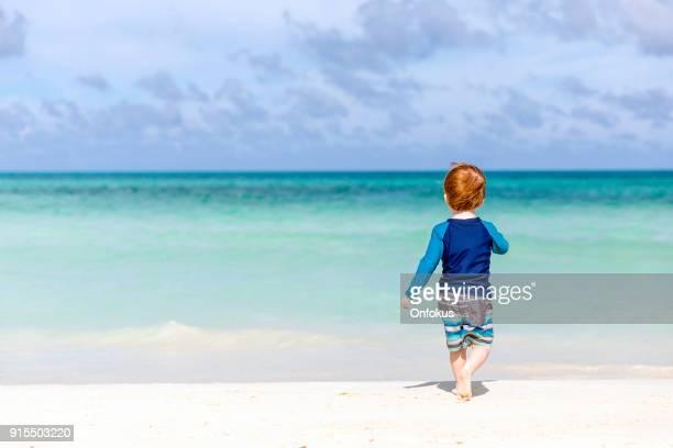 Baby Boy lopen op tropisch strand, Cayo Coco, Cuba