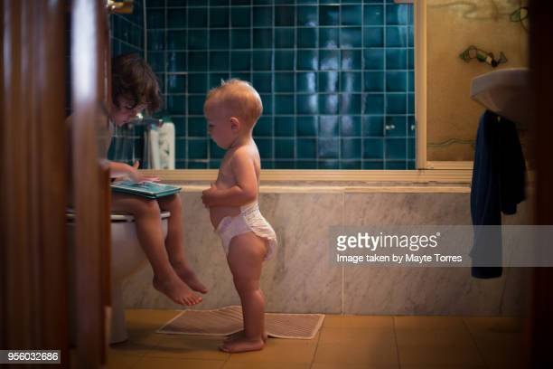 baby boy watches his brother play with a tablet in the toilet - familia desnuda fotografías e imágenes de stock