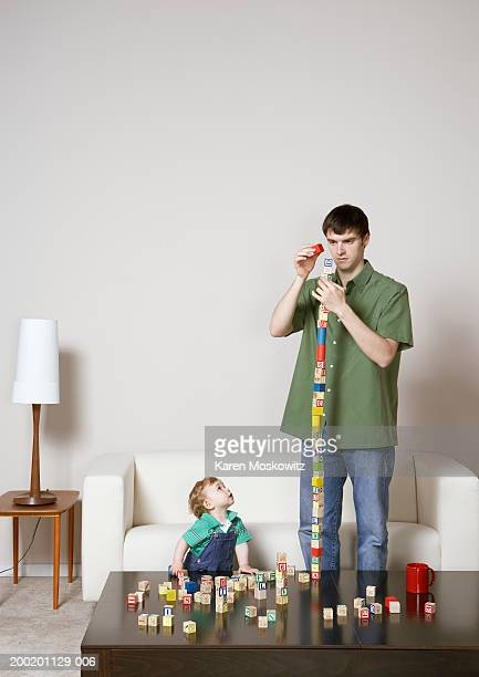 Baby boy (9-12 months) watching young man stack blocks on coffee table