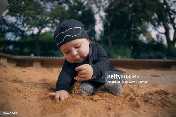 baby boy wearing a bat costume playing with sand