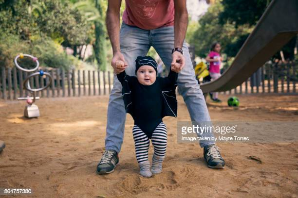 Baby boy wearing a bat costume with dad at the park