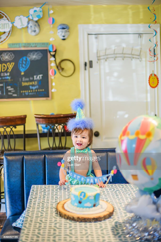 Baby Boy Wearing Party Hat With First Birthday Cake At Table Stock Foto