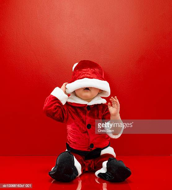 Baby boy (6-11 months) wearing Santa costume, studio shot