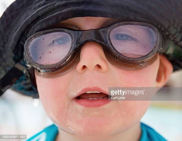 Baby boy (13-15 months) wearing swimming goggles and sun hat, close-up