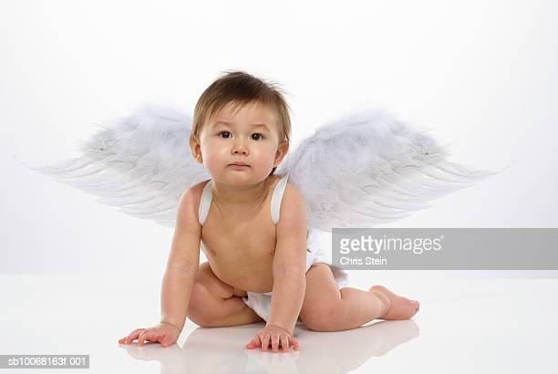 Baby boy (6-11 months) with angel wings, studio portrait