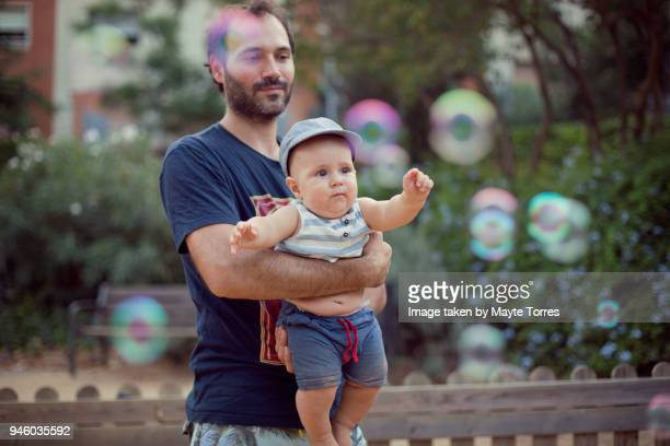 baby boy with dad trying to reach bubbles