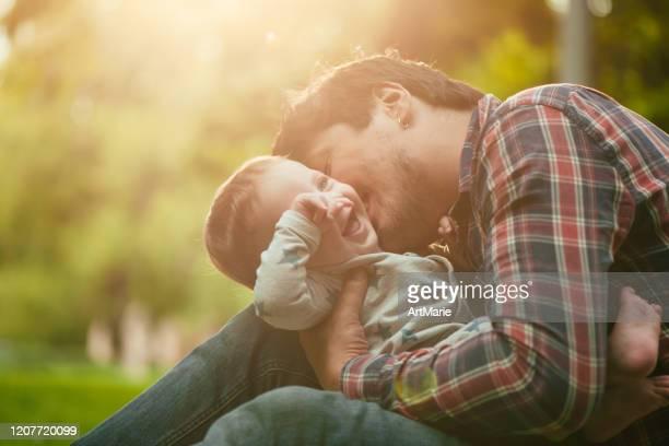 de jongen van de baby met is vader die van de de zomerdag geniet - kussen met de mond stockfoto's en -beelden