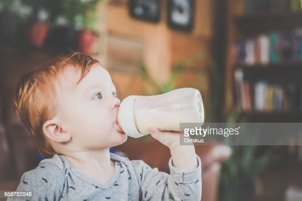 baby boy with milk bottle - milk bottle stock pictures, royalty-free photos & images