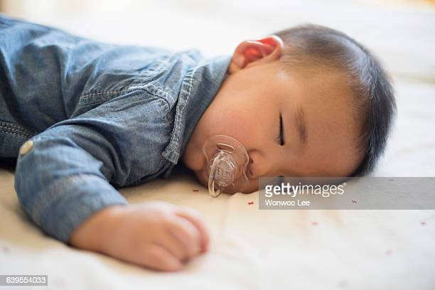 Baby boy with pacifier sleeping on bed
