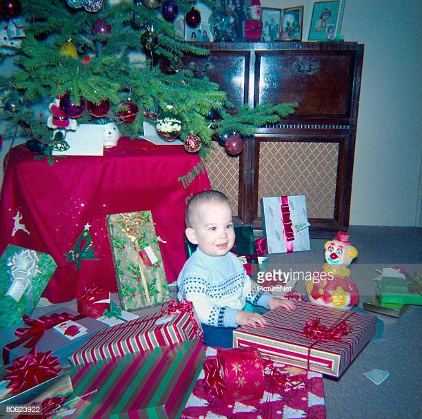 baby boy with presents at christmas tree - christmas past and christmas present stock pictures, royalty-free photos & images