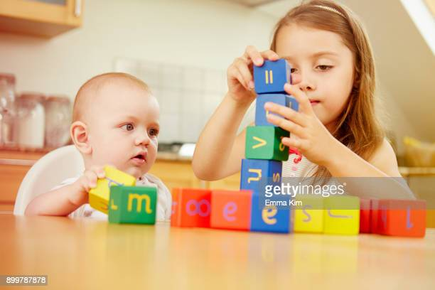Baby boy with sister, playing with colourful blocks