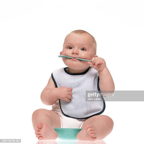 Baby boy (6-9 months) with spoon in mouth, portrait