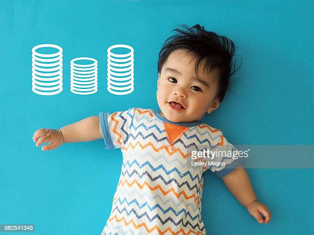 Baby boy with stacked coins in blue background