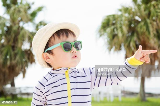 A baby boy with sunglasses striking a pose at seaside