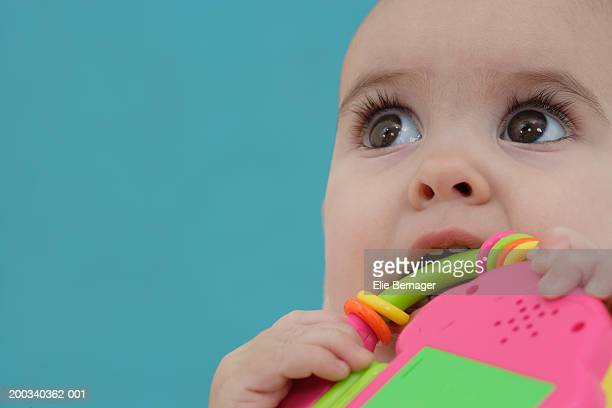Baby boy (6-9 months) with teething toy, looking up, close-up