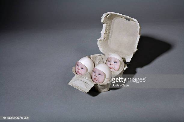 Baby boy's face on eggs in box (digital composite)