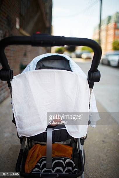 Baby boy's foot sticking out from under muslin in push chair