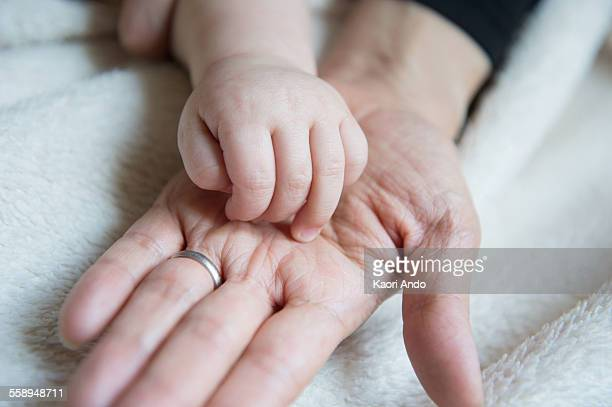 Baby boys hand resting on mothers hand, close-up